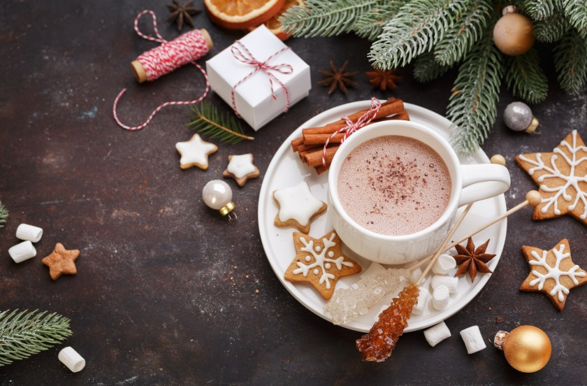 A cup of hot chocolate surrounded by Christmas decor and cookies