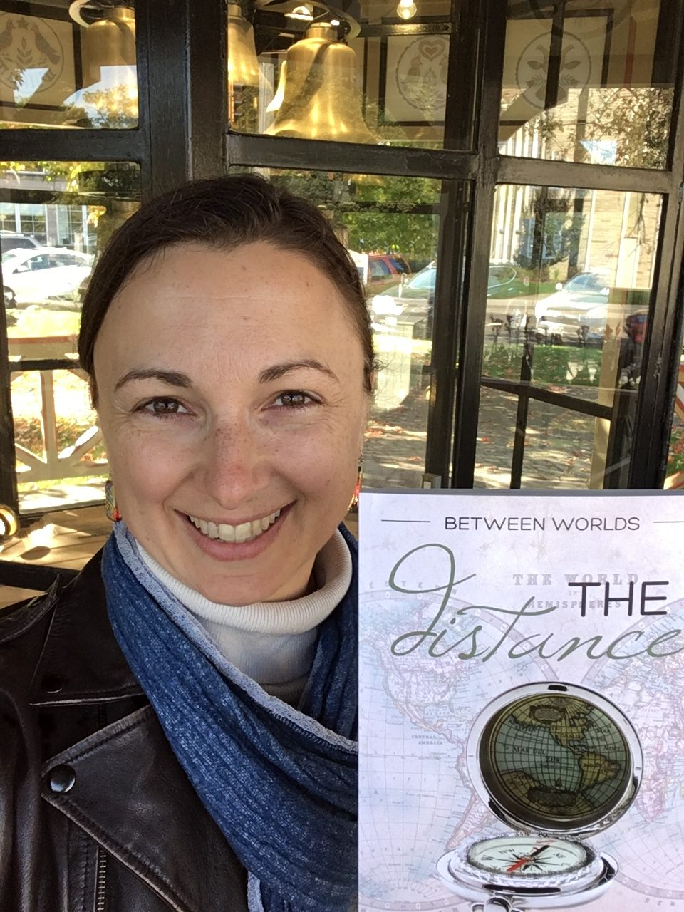 Lori Wolf-Heffner holding up a copy of Between Worlds 2: The Distance