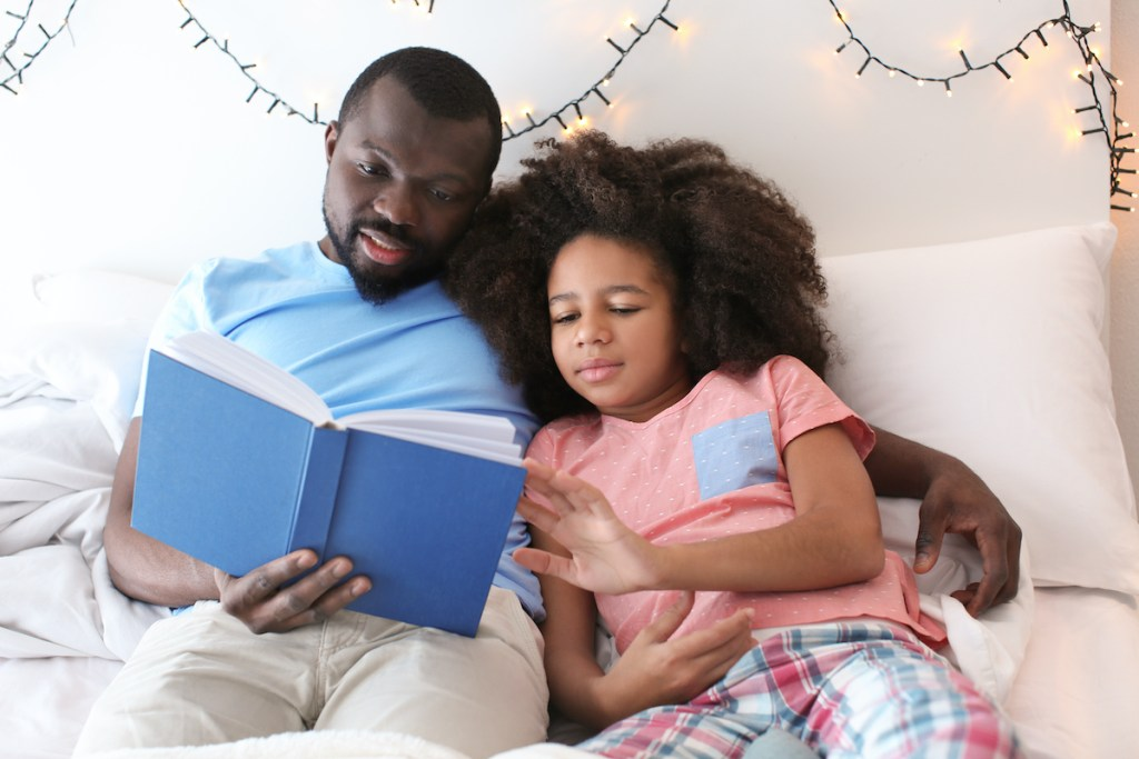 Father reading to his pre-teen daughter