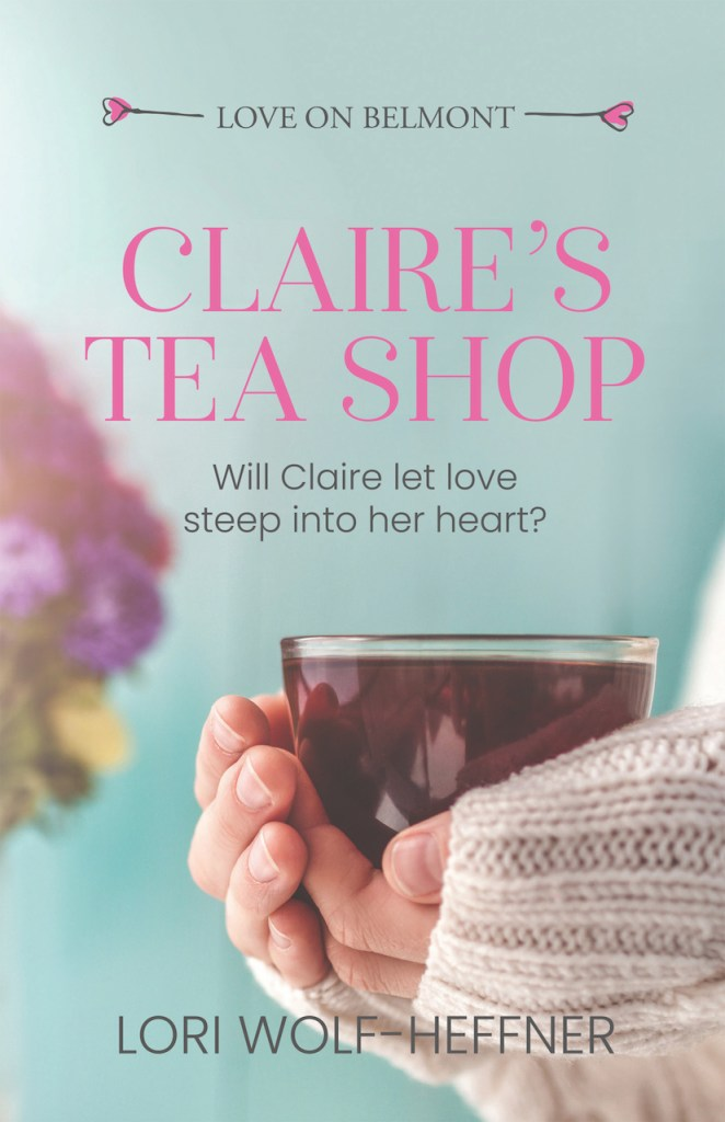 A woman's hands holding a glass mug of tea. The cover for Lori Wolf-Heffner's short story, Claire's Tea Shop