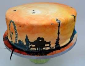London Skyline on cake, shillouette of couple on bench, london wedding cake, hand painted cake of london, london Eye cake, Big Ben cake, Birds on cake, sunset wedding cake, sunrise wedding cake,
