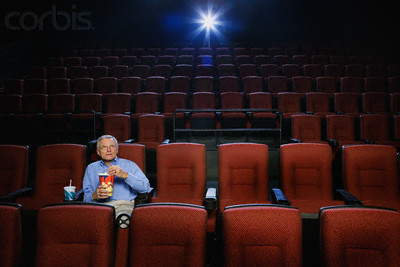 Man Watching a Movie in an Empty Theatre