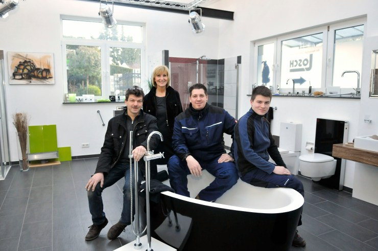 Das Team der Firma Detlef Losch Sanitärtechnik auf einer weißen Badewanne