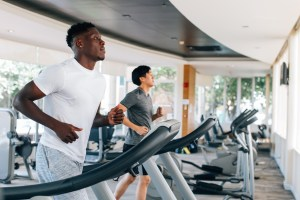 ethnic males running on treadmills