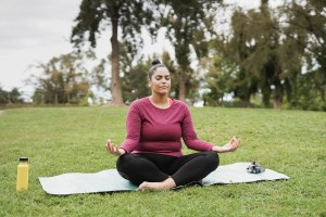 woman doing meditation at city park - Healthy lifestyle and life balance concept