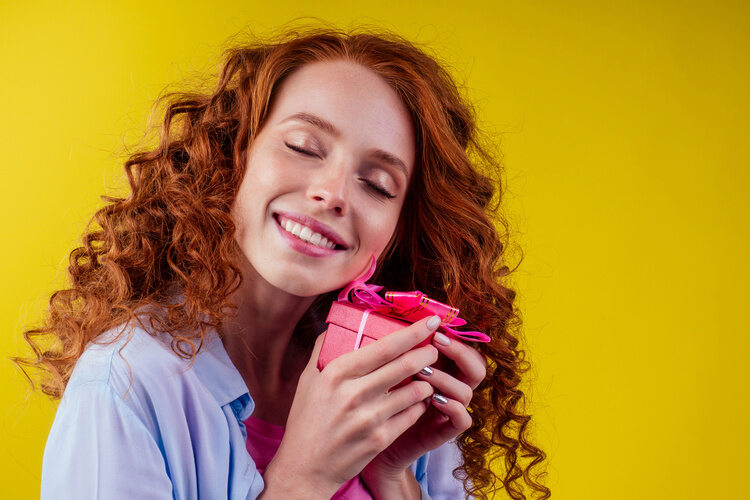 red haired woman holding gift box yellow background treat yourself