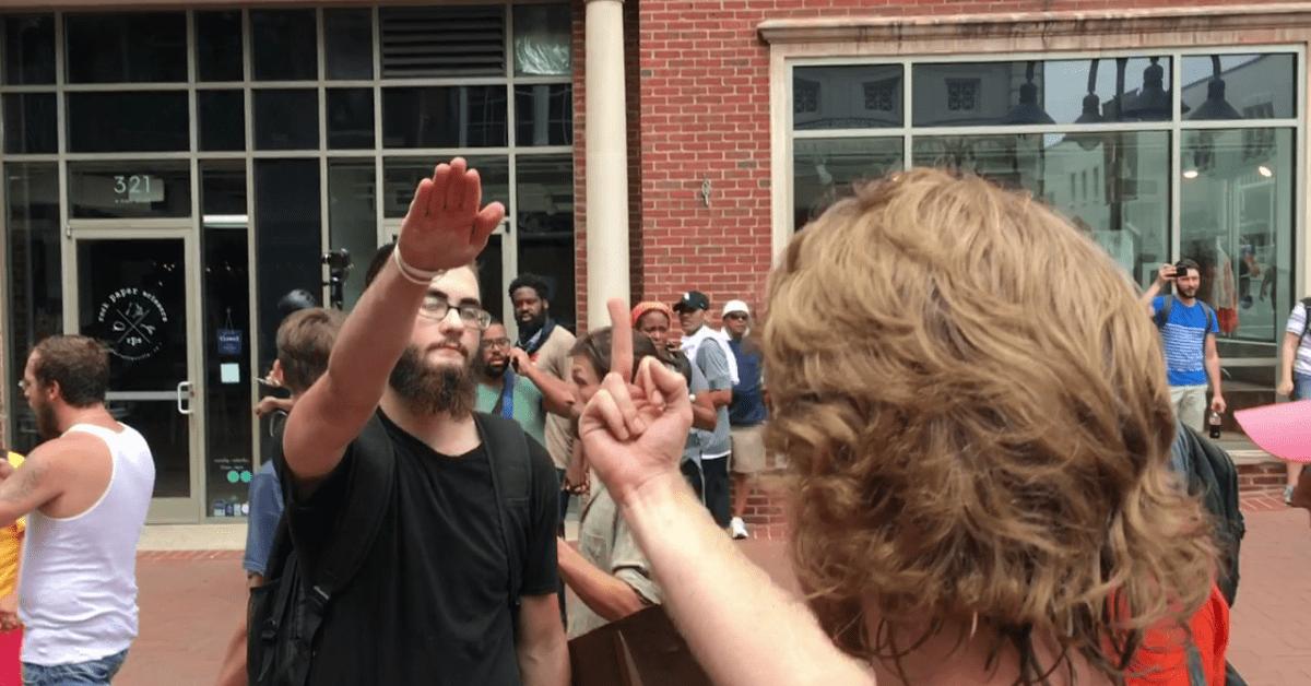 Il saluto fascista di un simpatizzante del terrorismo cristiano USA, cui risponde una donna, di spalle, mostrandogli il dito medio