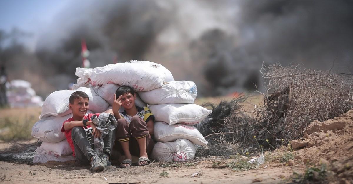 Due bambini della striscia di Gaza sorridono dietro un mucchio di sacchi messi per formare una trincea, alle loro spalle i fumi di una probabile esplosione