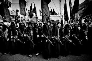 Una manifestazione jihadista a Gaza nel 2010: un insieme di persone di nero vestite, con lunghe tonache e veli a coprire quasi interamente il volto, sfilano imbracciando dei fucili