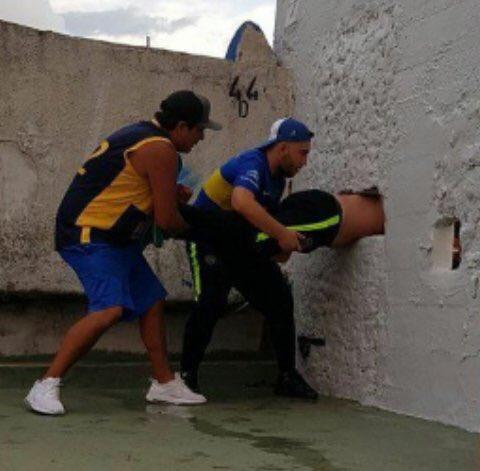 Aficionado, Boca Juniors, se atora, pared, estadio bombonera, al tratar, de llegar a otra zona, lo sacan, con raspones