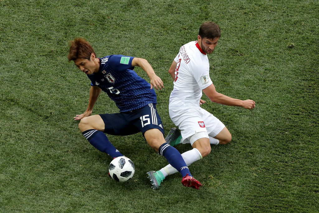 VOLGOGRAD, RUSSIA - JUNE 28: Yuya Osako of Japan is tackled by Bartosz Bereszynski of Poland during the 2018 FIFA World Cup Russia group H match between Japan and Poland at Volgograd Arena on June 28, 2018 in Volgograd, Russia.