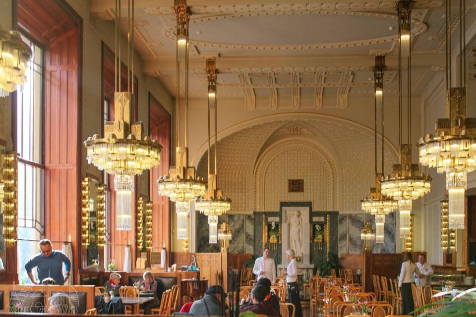 Interior del café art noveau de la Casa Municipal. Lamparas de cristal a los lados, mesas en el centro y bancos en las dos pares de la imagen. Techos con decoraciones de yeso y grandes ventanales a la izquierda.