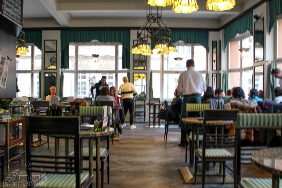 El café cubista en su interior. Tonos verdes, lámparas en estilo cubista. Grandes ventanales que lo rodean todo. Gente sentada en algunas de las mesas.