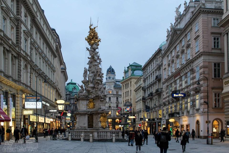 Columna de la Peste en medio de una pequeña plaza. A los lados, edificios de corte clásico despuntando al final a la derecha uno de más moderno.