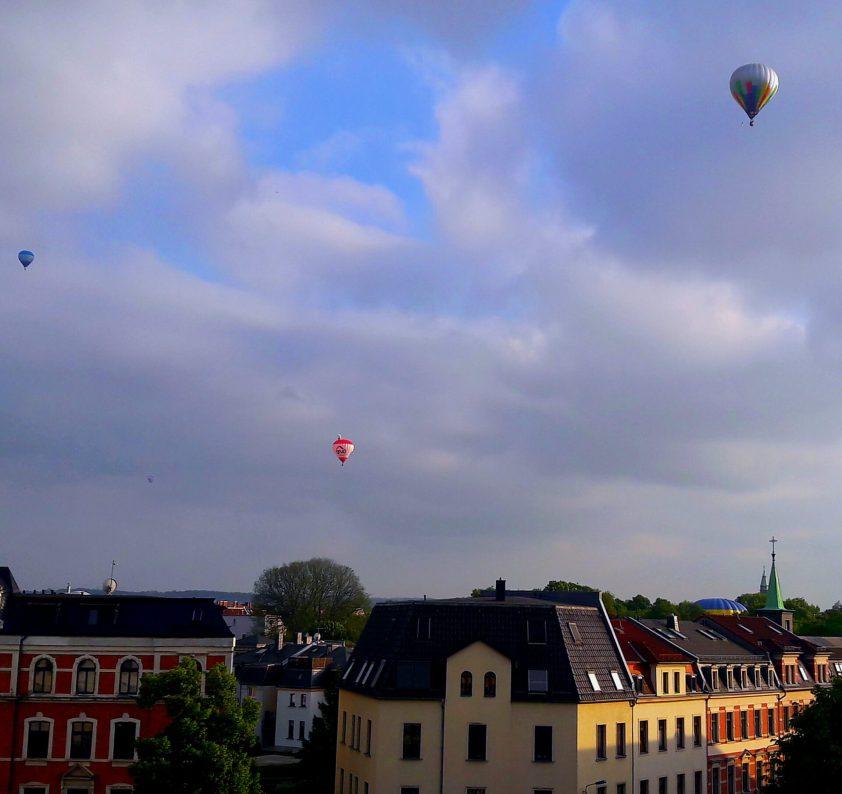 Blick über die Dächer Zwickaus, während anlässlich des Ballonfestivals mehrere Heißluftballons am Himmel zu sehen sind