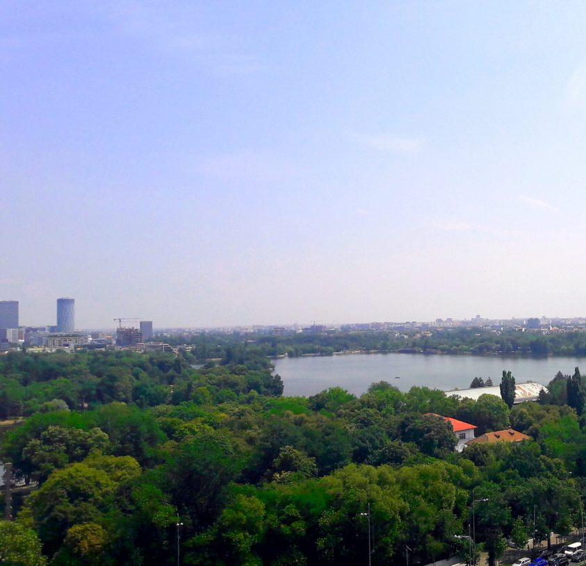 Losprobiert in Rumänien: Blick über den Herastrau-Park in Bukarest, zu sehen sind viele Bäume, der große See und im Hintergrund die Skyline der Stadt
