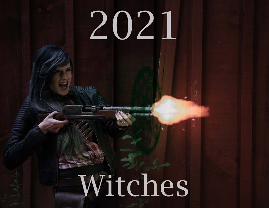 Lossien is on the left of the photo with grey hair, wearing a red plaid shirt and black leather jacket. She is screaming as she fires a shotgun, the shotgun has a blast coming out of it and a magical sigil at the end of the barrel. The top says '2021' and the bottom says 'Witches'.