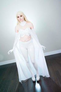 Lossien in white PVC crop top, pants and gloves with a blonde wig and a white cape.