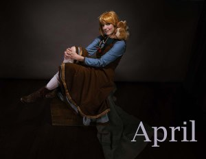 Lossien dressed as Twiggy. She is sitting on a box, wearing a brown dress with a blue underdress. There is a squirrel stuffed animal on her shoulder, and she is wearing a blonde wig with twigs in her hair. The word 'April' appears on the bottom right.