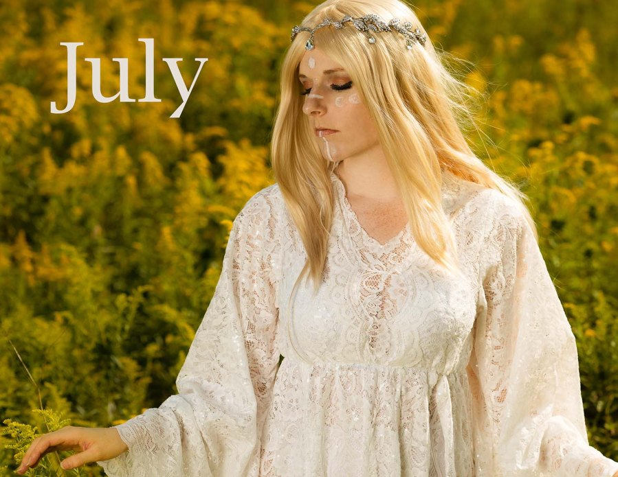Lossien is wearing a white lace dress and blonde wig with silver diadem and white face markings in the shape of moon cycles. She is standing in a field of yellow flowers, with the word 'July' on the top left.