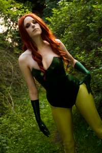 Lossien in the forest, dressed as Poison Ivy, with red hair, light green tights, and a dark green bodysuit and matching gloves. One hand on her hip.