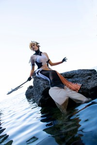 Lossien as a mermaid, sitting on a rock in the water. She is holding a spear to one side. She has blonde hair with a gold crown, and black and white suit and tail with gold details.