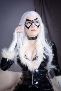 Lossien in a black PVC bodysuit in a close up, with fur trimming around the bust and sleeves. She is wearing a black mask and white hair.