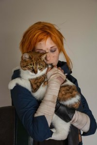 Lossien in an orange wig, holding a cat on her shoulder closer to camera. The cat is white and orange.