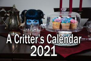 A well laid table, with a silver teapot, fancy cups, and a display of pink and blus cupcakes. lossien, as Jester, peeks up from behind the table, eyeing the cupcakes. Text reads, across the bottom front '2021 Critter Calendar'.