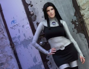 Lossien standing against a graffitied wall, wearing a black wig, a silver bodysuit, and a black cropped shirt and skirt over the bodysuit.