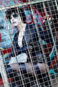 Lossien behind a metal gate, wearing a navy bodysuit with a white face and black painted over one eye. With a short black wig on.