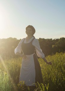 Lossien in a field as Belle, with the sun shinning in brightly on the left side. Wearing a blue dress with white undershirt and apron, and a brown wig.