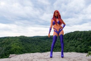 Lossien as Starfire, on the edge of a cliff. With long red hair, orange skin and a purple bikini with tall purple boots and arm detailing.