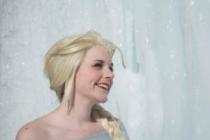 A close up of Lossien as Elsa, with a light blonde wig, standing in front of a wall of ice.