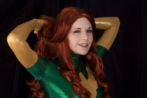 A close up of Lossien in a green bodysuit with a red wig, playing with her hair.
