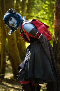 Lossien as Jester, leaning against a tree and bent forward. She has blue skin, hair and horns, and is wearing a blue and grey dress with a bright pink backpack.