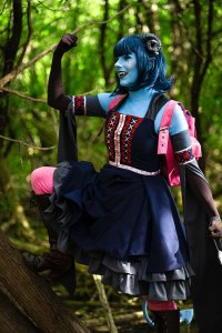 Lossien as Jester, with on leg up on a tree and one arm up in victory. Blue skin and hair, brown gloves and boots, bright pink pants and backpack, and a grey and blue dress on.