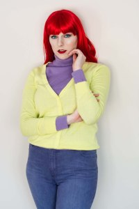 Lossien as Mary Jane, in a bright red wig, a purple sweater, yellow cardigan, and purple jeans.