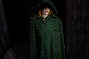 A green cloaked figure with slight orange hair peaking out.