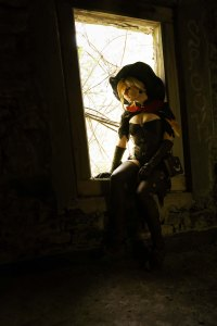 Lossien sitting in a window in a darkly lit room, wearing a witch Mercy costume. She has a large broon witch hat, a blonde wig, a black jacket, and brown gloves, corset, thigh high stockings, and boots.