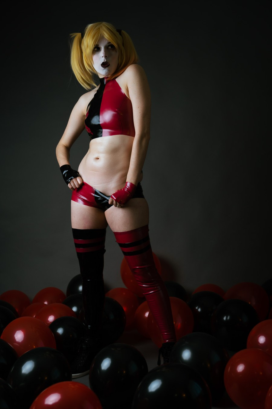 Lossien as Harley in red and black latex cropped shirt, small pants, and thigh high leggings. She is resting her hands on the waistband of her shorts, pulling them down playfully, while standing in a bunch of black and red balloons.