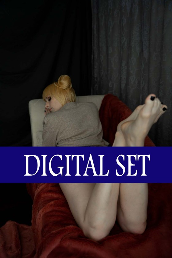 Lossien laying away from camera, on hr stomach, in a blonde wig with buns, and a tan cardigan. her bum is obscured by a navy bar that reads 'Digital Set' in white.