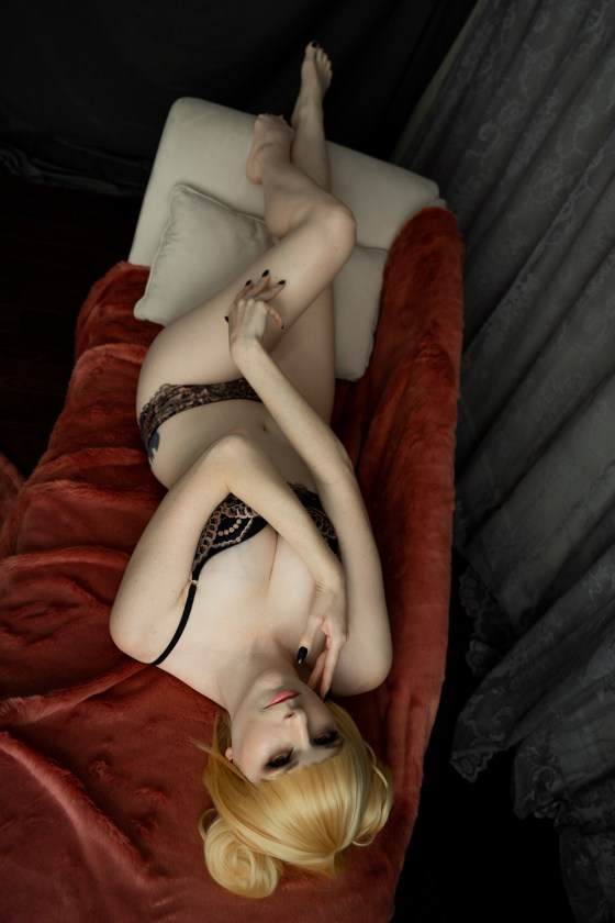 Lossien lays on her back, head toward camera, wearing a blonde wig with two buns. She has on black and tan lingerie, and is wrapping her arms around herself, one hand on her neck, another on her crossed legs.
