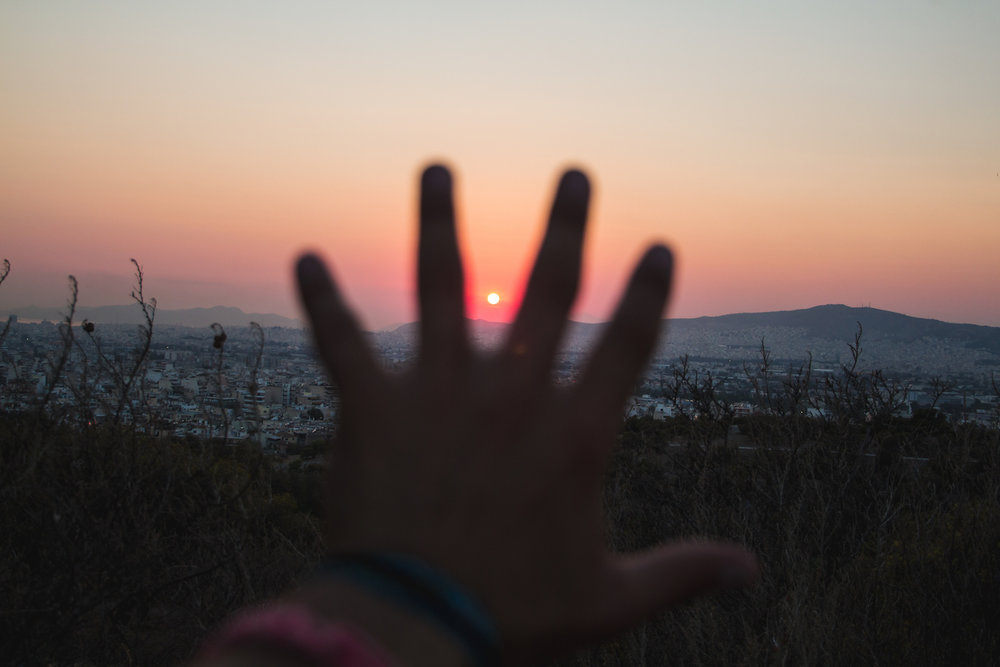 Photo of a silhouetted hand and the sunset over Athens Greece.