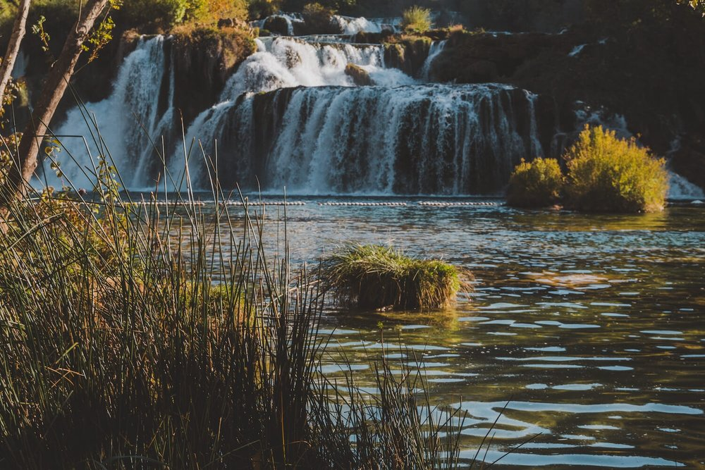Waterfalls of Krka National Park Croatia. Photo taken with Canon 650D Rebel T4i, edited in Lightroom. Get the free Krka lightroom preset with cool highlights, warm shadows, and a gentle fade.