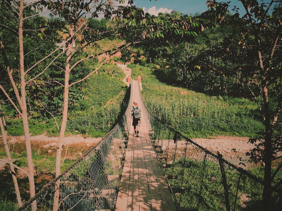 Photo of Ryan walking across the suspension bridge in Camp-Perrin Haiti that crosses a river.