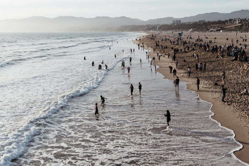 Photo of Santa Monica Beach at sunset with rolling waves and silhouettes of people on the beach.