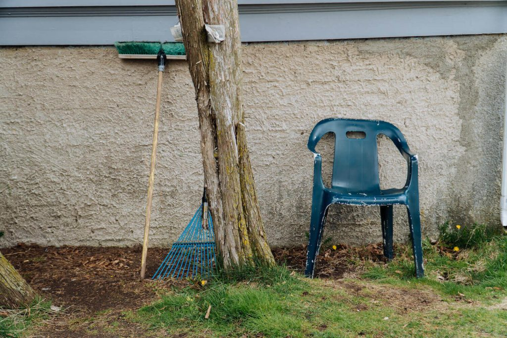 Photo of a plastic chair at a house with a rake and newspaper.