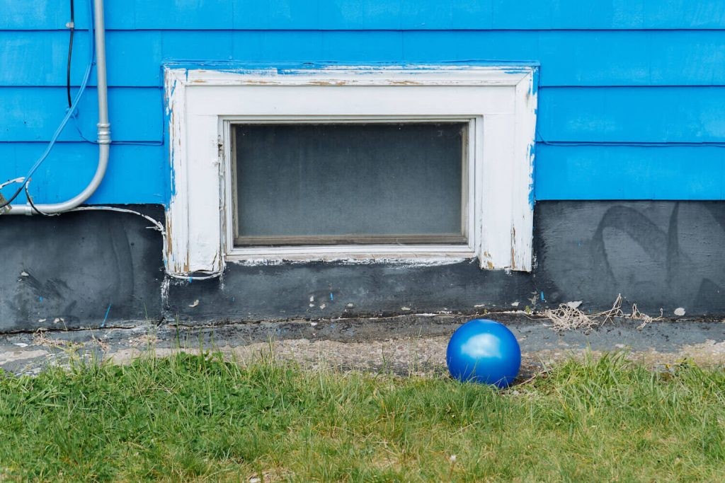 Photo of a shiny blue ball on a green lawn with a blue house behind.
