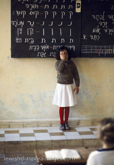 Photograph of Jewish girl reciting a lesson in the Jewish community school classroom in Fez (Fes), Morocco. The girl stands at front of classroom in front of a blackboard with Hebrew alphabet. The education is multilingual, including French, Arabic, and Hebrew studies, reflecting some of the cultures of the Jewish diaspora. Photograph by Nathan Benn taken February 15, 1980.